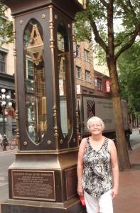 Standing beside a 'steam clock' on a street in Gastown.
